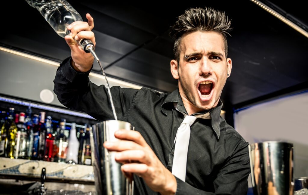 Photo of bartender free-pouring a mixed drink