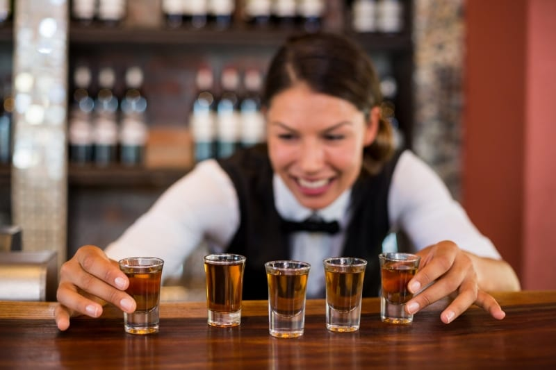 Photo of bartender with shot glasses